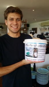 Friend Evan Batkin with a fundraising bucket at Penny Whistlers cafe